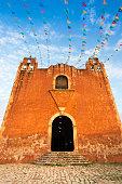 Santa Elena, Yucatan, Mexico: A vibrant sunlit orange church in Spanish Colonial style (shot at sunset) in Santa Elena, a Mayan village 10 kilometers from the Mayan Uxmal ruins in the Yucatan Peninsul