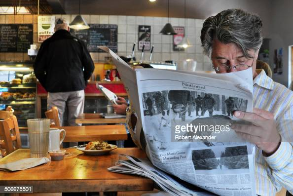 Santa Fe New Mexico resident reads a Sunday New York Times newspaper at Downtown Subscription coffee bar and newstand a popular gathering place in...
