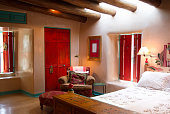"Santa Fe style: colorful rustic-chic bedroom with viga beams, thick adobe walls that are hand-troweled with a ""diamond-hard finish,"" red shutters and doors, turquoise trim."