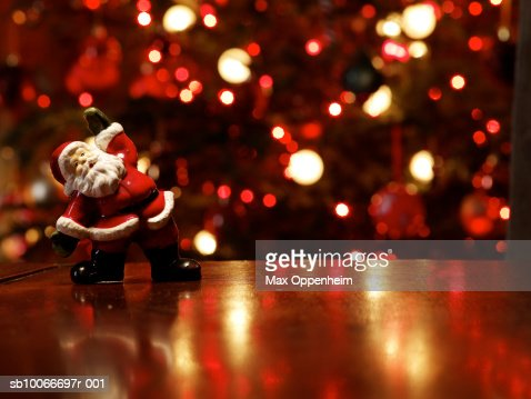 Santa figurine on table in front of Christmas tree : Foto de stock