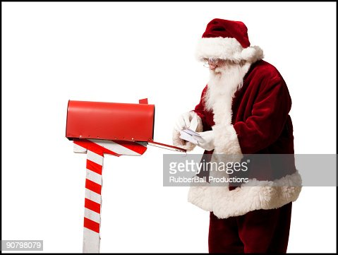 santa getting mail out of his mailbox : Stock Photo