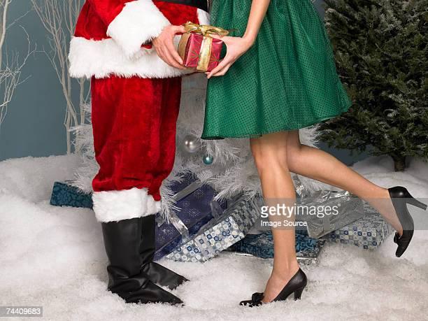 Santa handing a present to a woman