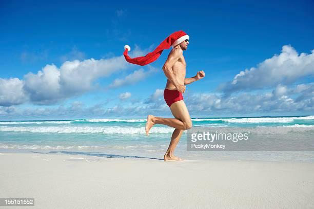 Santa Chapéu homem em execução na praia de férias de Natal