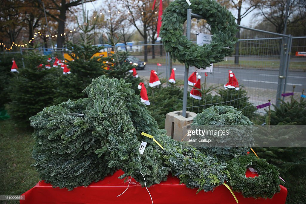Santa hats decorate Christmas trees and wreaths lie on a table on display at an outdoor Christmas tree market on November 20, 2013 in Berlin, Germany. With Christmas still over a month away, the city of Berlin is already busy preparing for the holiday.