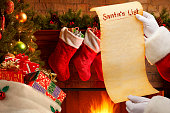 Santa holds a blank Christmas list made of parchment in front of a beautifully decorated Christmas tree, Santa's bag, and fireplace inside someone's home.