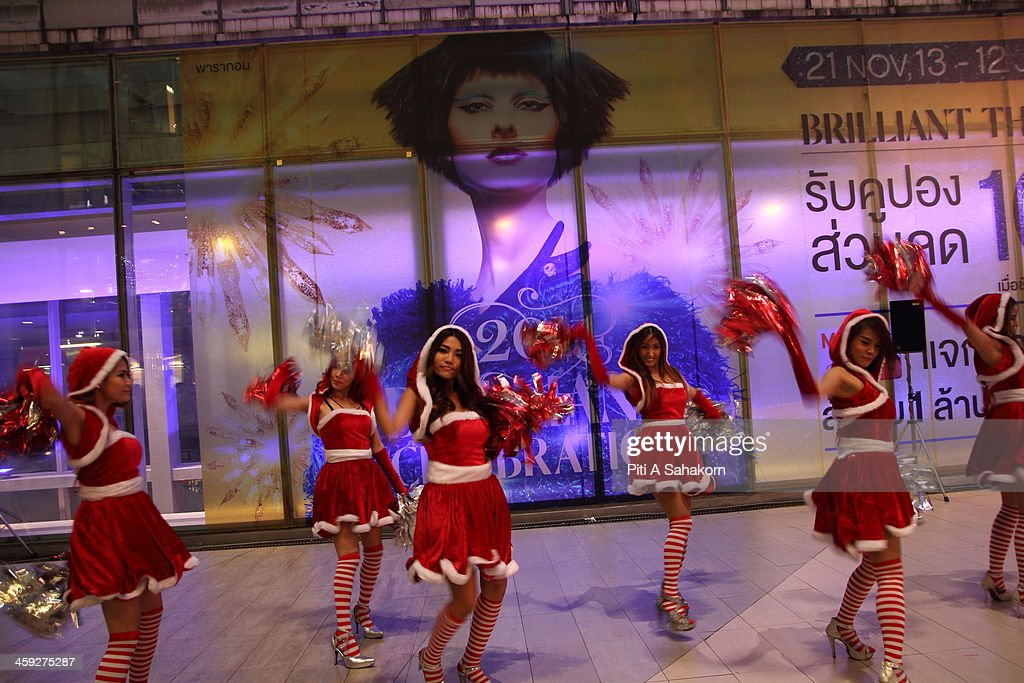 Santa ladies performing near a advertisment screen at Siam Paragon shopping mall in Bangkok.