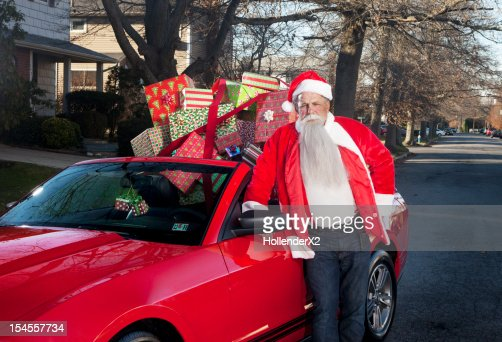 Santa leaning on convertible full of presents : Foto de stock