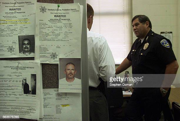 Santa Paula Police Chief Bob Gonzales talks with Detective Daryl Koranda behind wall with wanted fliers at the Santa Paula Police station Digital...
