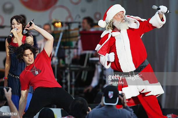 Santa performs some 'crumping' dance moves with Drew Neemia of Sticky TV live on stage during CocaCola Christmas In The Park at Auckland Domain on...