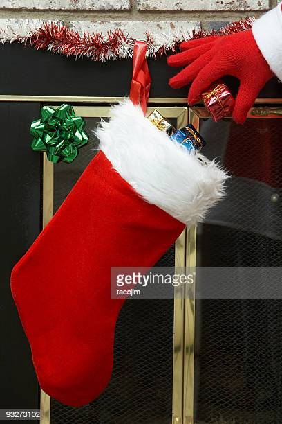 Santa putting presents in a Christmas stocking