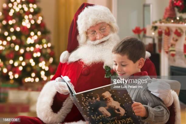 Santa reading book to Caucasian boy