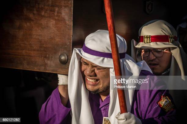 Santa Semana procession participants straining under weight of religious float (anda) -  Antigua, Guatemala