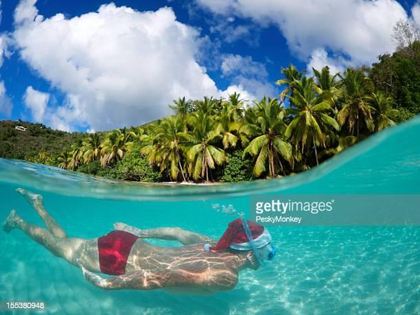 Santa nada subaquática com Equipamento de Mergulho Livre nas férias tropicais