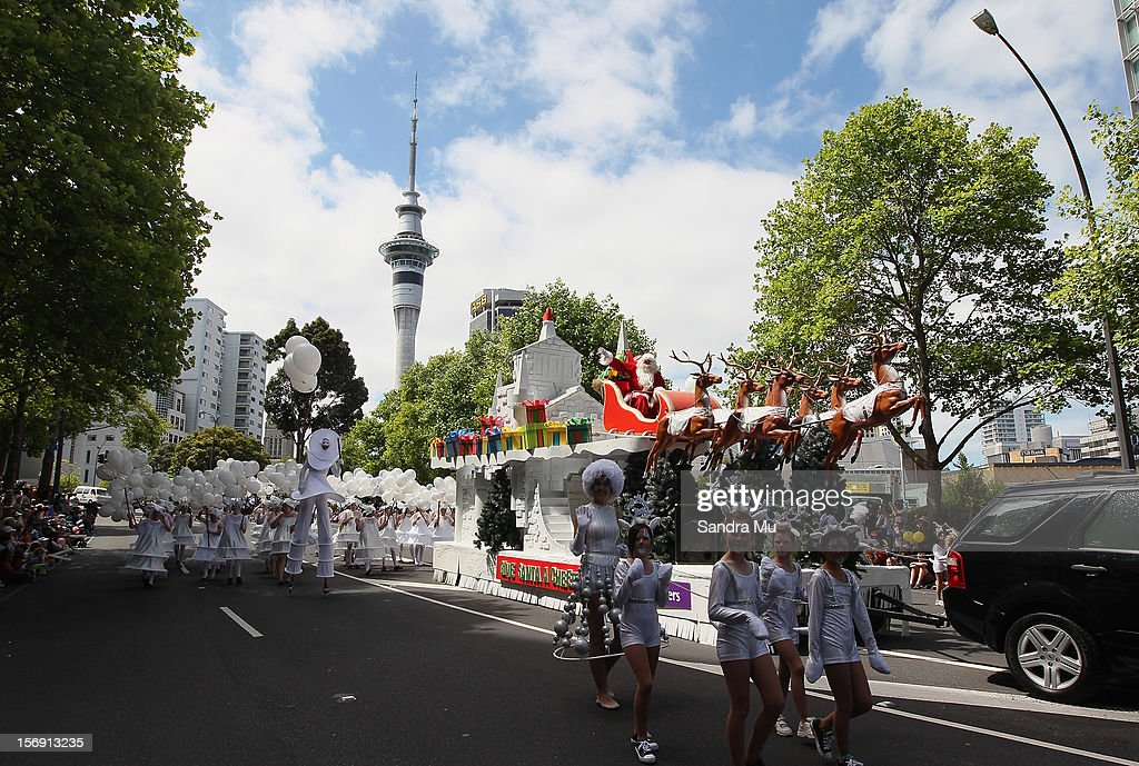 Santa waves to the thousands of people lining the street to watch the annual Farmers Santa Parade on November 25, 2012 in Auckland, New Zealand. For 78 years the Farmers Santa Parade has brought joy to the children of Auckland marking the start of the Christmas season.