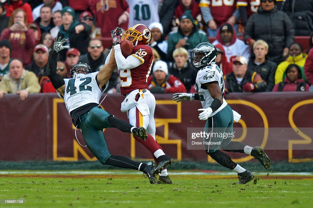 <a gi-track='captionPersonalityLinkClicked' href=/galleries/search?phrase=Santana+Moss&family=editorial&specificpeople=204490 ng-click='$event.stopPropagation()'>Santana Moss</a> #89 of the Washington Redskins catches a pass for a touchdown in between <a gi-track='captionPersonalityLinkClicked' href=/galleries/search?phrase=Kurt+Coleman+-+American+Football+Player&family=editorial&specificpeople=15191225 ng-click='$event.stopPropagation()'>Kurt Coleman</a> #42 and <a gi-track='captionPersonalityLinkClicked' href=/galleries/search?phrase=Brandon+Boykin&family=editorial&specificpeople=5610340 ng-click='$event.stopPropagation()'>Brandon Boykin</a> #22 of the Philadelphia Eagles at FedEx Field on November 18, 2012 in Landover, Maryland. The Redskins won 31-6.