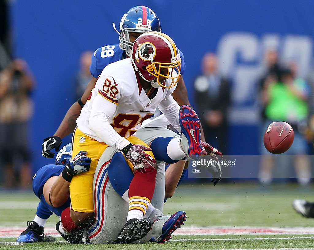 Santana Moss of the Washington Redskins fumbles the ball as he is hit by Chase Blackburn of the New York Giants on October 21 2012 at MetLife Stadium...