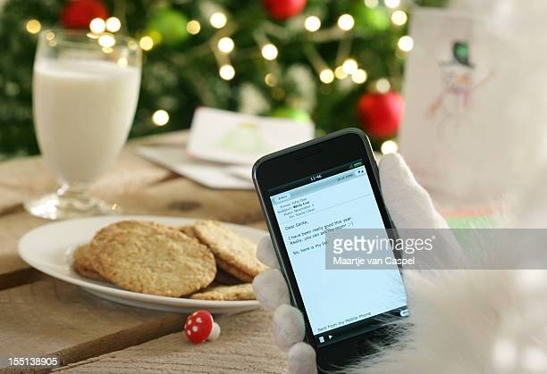 Santa's gloved had reading email next to milk and cookies