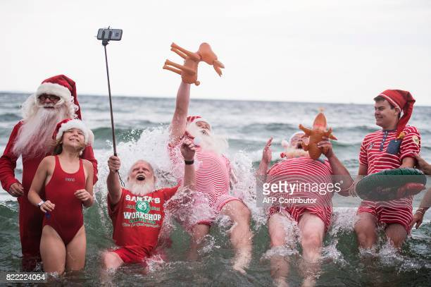 TOPSHOT Santas jump for a picture into the water at the amusement park Dyrehavsbakken in Klampenborg north of Copenhagen on July 25 2017 Since 1957...