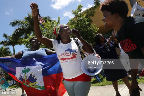 Santcha Etienne and others protest in front of the United States Citizenship and Immigration Services office in Broward county to urge the Department...