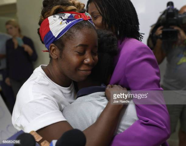 Santcha Etienne hugs a 10yearold girl who was afraid to have name used and her face shown after speaking to the media about the Temporary Protected...