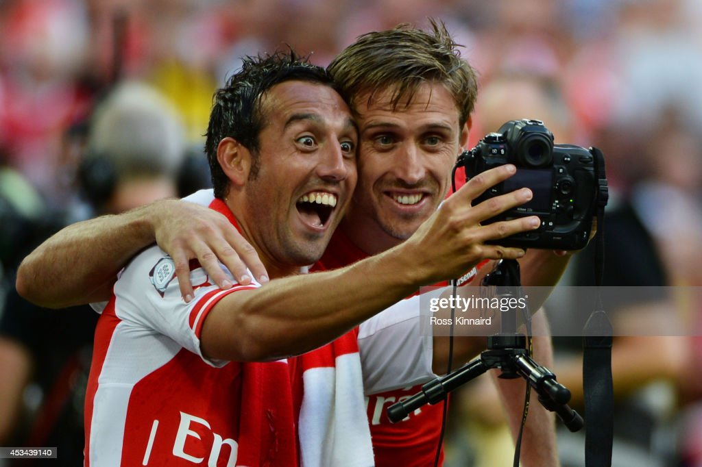Santi Cazorla of Arsenal and team-mate Nacho Monreal (R) take a photo together during the FA Community Shield match between Manchester City and Arsenal at Wembley Stadium on August 10, 2014 in London, England.