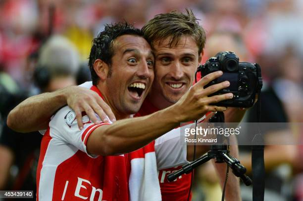Santi Cazorla of Arsenal and teammate Nacho Monreal take a photo together during the FA Community Shield match between Manchester City and Arsenal at...
