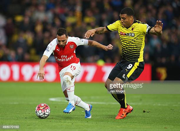 Santi Cazorla of Arsenal and Troy Deeney of Watford compete for the ball during the Barclays Premier League match between Watford and Arsenal at...