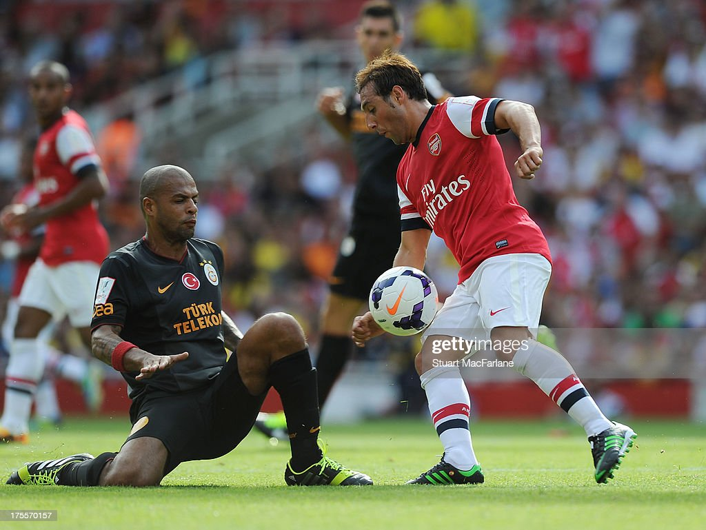 Santi Cazorla of Arsenal breaks past Felipe Melo of Galatasaray during the Emirates Cup match between Arsenal and Galatasaray at the Emirates Stadium on August 04, 2013 in London, England.