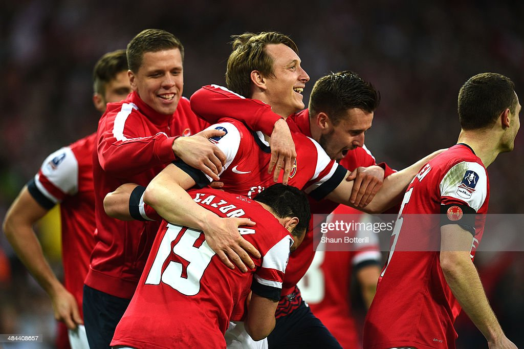 Santi Cazorla of Arsenal celebrates with team mates after scoring their winning penalty during the FA Cup Semi-Final match between Wigan Athletic and Arsenal at Wembley Stadium on April 12, 2014 in London, England.