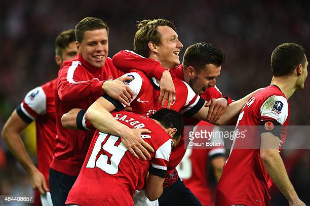 Santi Cazorla of Arsenal celebrates with team mates after scoring their winning penalty during the FA Cup SemiFinal match between Wigan Athletic and...