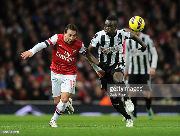 Santi Cazorla of Arsenal challenges Cheick Tiote of Newcastle during the Barclays Premier League match between Arsenal and Newcastle United at...