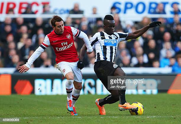 Santi Cazorla of Arsenal challenges Cheick Tiote of Newcastle United during the Barclays Premier League match between Newcastle United and Arsenal at...