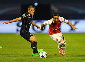 Santi Cazorla of Arsenal goes past Arijan Ademi of Dinamo Zagreb during the UEFA Champions League Group F match between Dinamo Zagreb and Arsenal at...