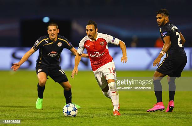 Santi Cazorla of Arsenal goes past El Arabi Hilal Soudani and Arijan Ademi of Dinamo Zagreb during the UEFA Champions League Group F match between...