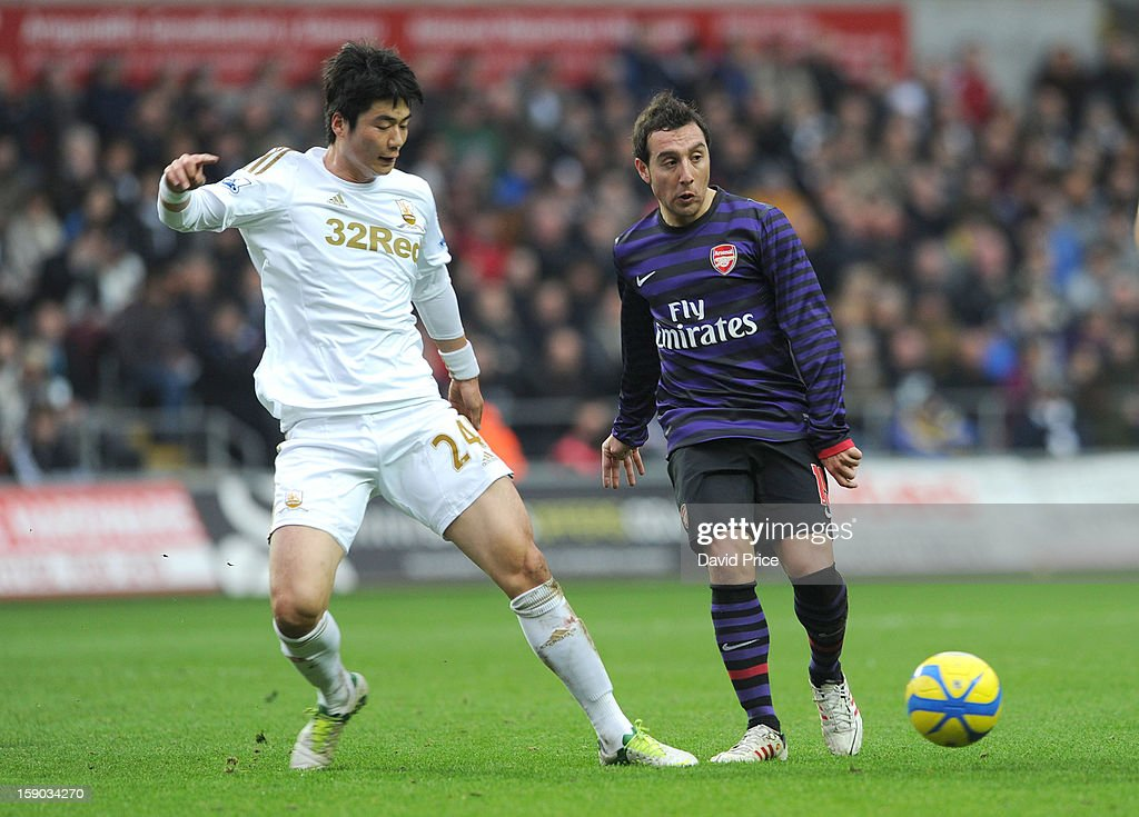 Santi Cazorla of Arsenal is closed down by Ki Sung-Yueng of Swansea during the FA Cup Third Round match between Swansea City and Arsenal at the Liberty Stadium on January 6, 2013 in Swansea, Wales.