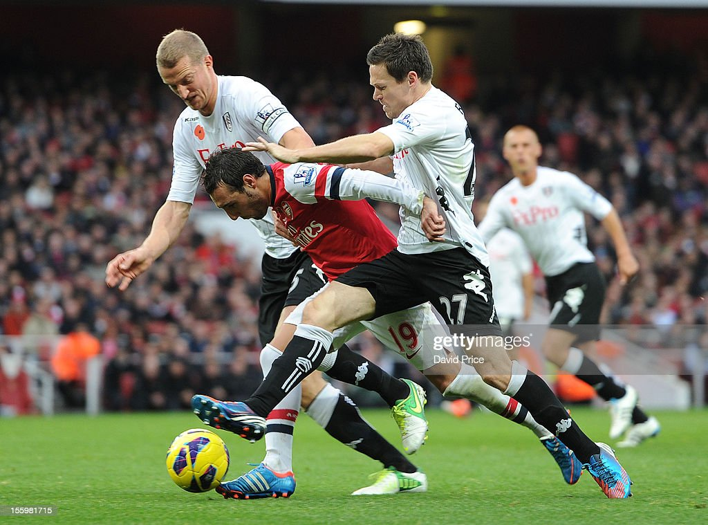 <a gi-track='captionPersonalityLinkClicked' href=/galleries/search?phrase=Santi+Cazorla&family=editorial&specificpeople=709830 ng-click='$event.stopPropagation()'>Santi Cazorla</a> of Arsenal is fouled by <a gi-track='captionPersonalityLinkClicked' href=/galleries/search?phrase=Brede+Hangeland&family=editorial&specificpeople=618174 ng-click='$event.stopPropagation()'>Brede Hangeland</a> and <a gi-track='captionPersonalityLinkClicked' href=/galleries/search?phrase=Sascha+Riether&family=editorial&specificpeople=614139 ng-click='$event.stopPropagation()'>Sascha Riether</a> of Fulham during the Barclays Premier League match between Arsenal and Fulham, at Emirates Stadium on November 10, 2012 in London, England.