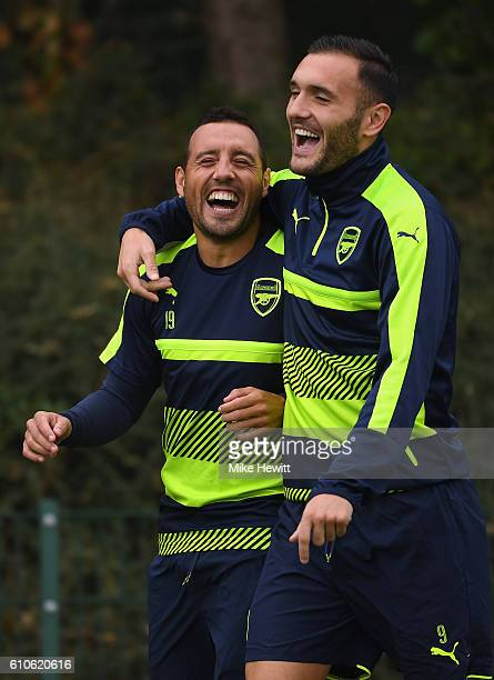 Santi Cazorla of Arsenal laughs with Lucas Perez during an Arsenal training session ahead of the Champions League Group A match between Arsenal and...