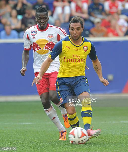 Santi Cazorla of Arsenal takes on Ambroise Oyongo of New York Red Bulls the pre season match between New York Red Bulls and Arsenal at Red Bull Arena...