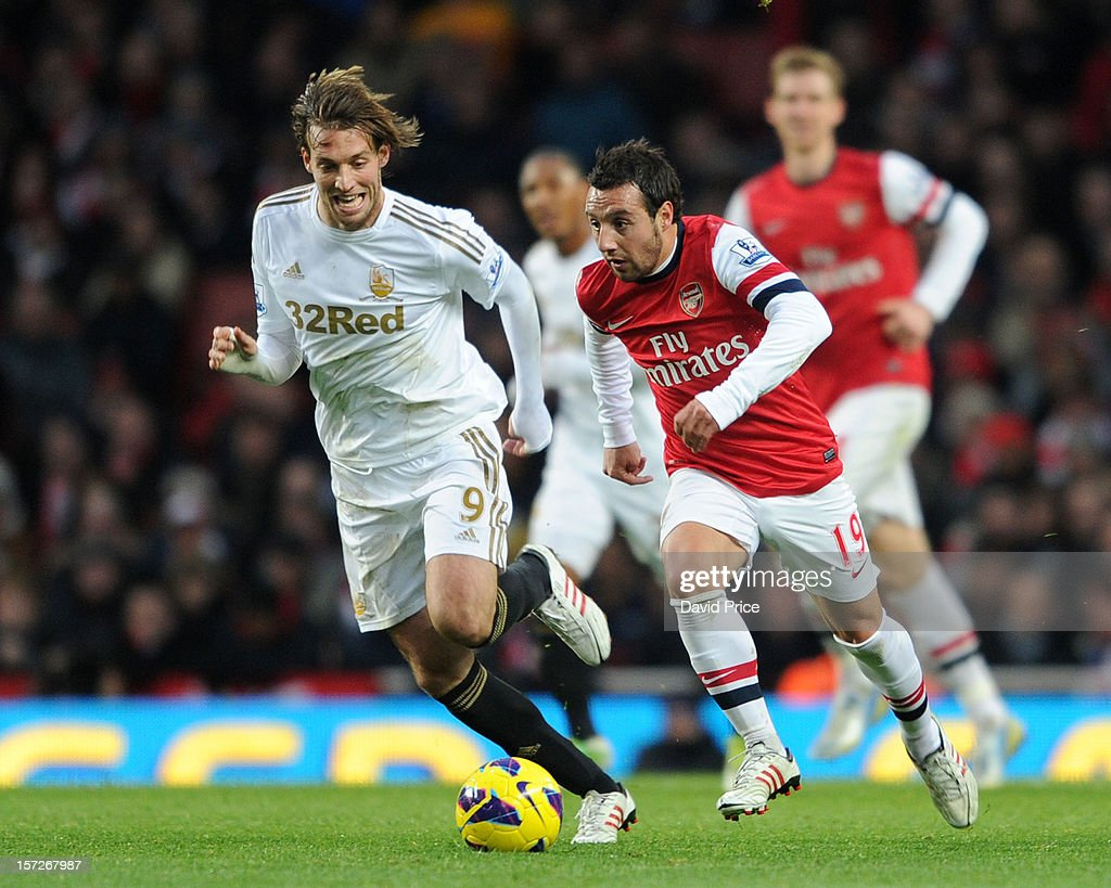 <a gi-track='captionPersonalityLinkClicked' href=/galleries/search?phrase=Santi+Cazorla&family=editorial&specificpeople=709830 ng-click='$event.stopPropagation()'>Santi Cazorla</a> of Arsenal takes on Miguel <a gi-track='captionPersonalityLinkClicked' href=/galleries/search?phrase=Michu+-+Voetballer&family=editorial&specificpeople=9691137 ng-click='$event.stopPropagation()'>Michu</a> of Swansea during the Barclays Premier League match between Arsenal and Swansea City, at Emirates Stadium on December 01, 2012 in London, England.