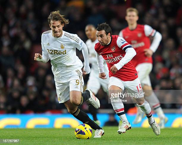 Santi Cazorla of Arsenal takes on Miguel Michu of Swansea during the Barclays Premier League match between Arsenal and Swansea City at Emirates...