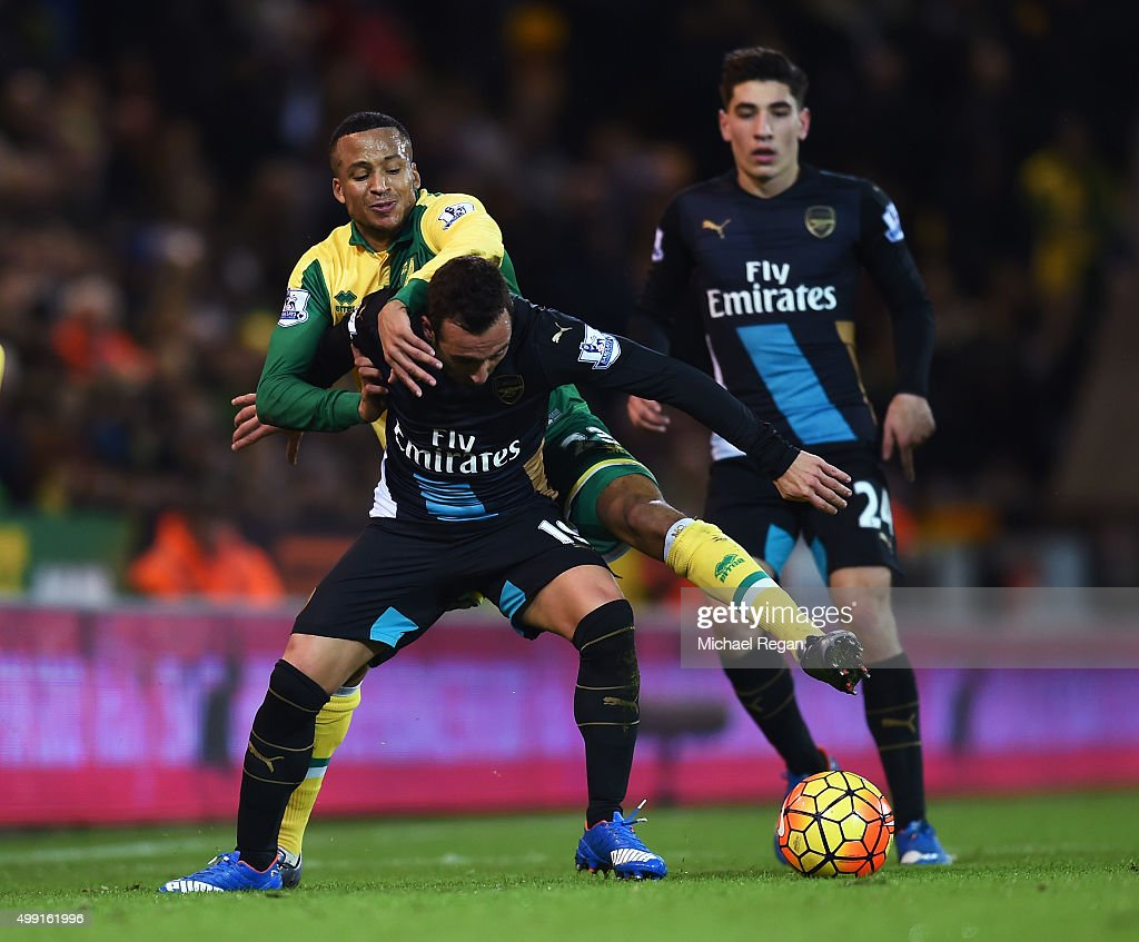 <a gi-track='captionPersonalityLinkClicked' href=/galleries/search?phrase=Santi+Cazorla&family=editorial&specificpeople=709830 ng-click='$event.stopPropagation()'>Santi Cazorla</a> of Arsenal tussles with <a gi-track='captionPersonalityLinkClicked' href=/galleries/search?phrase=Martin+Olsson&family=editorial&specificpeople=4185617 ng-click='$event.stopPropagation()'>Martin Olsson</a> of Norwich City during the Barclays Premier League match between Norwich City and Arsenal at Carrow Road on November 29, 2015 in Norwich, England.