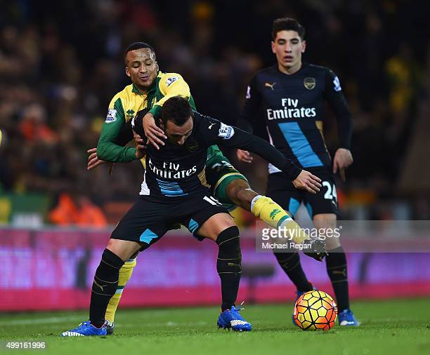 Santi Cazorla of Arsenal tussles with Martin Olsson of Norwich City during the Barclays Premier League match between Norwich City and Arsenal at...