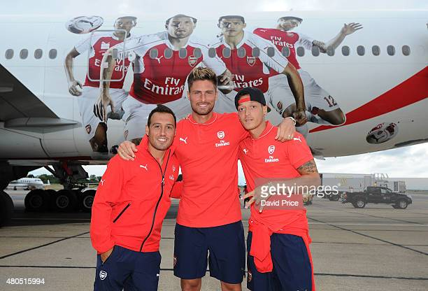 Santi Cazorla Olivier Giroud and Mesut Ozil of Arsenal in front of their images on the Emirates plane at Stansted Airport on July 12 2015 in London...