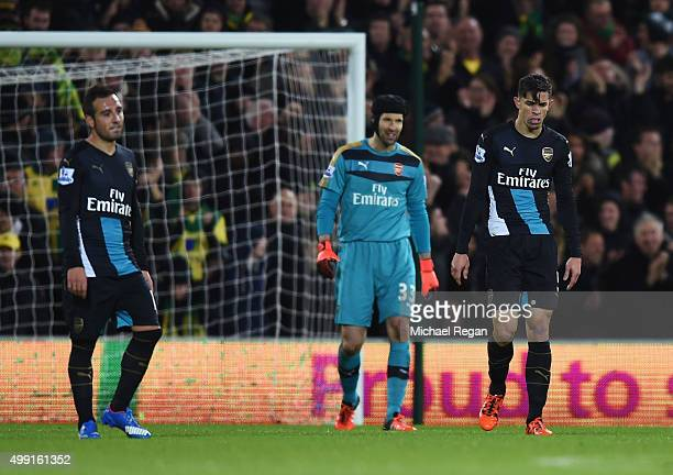 Santi Cazorla Petr Cech and Gabriel Paulista of Arsenal look dejected as Lewis Grabban of Norwich City scores their first and equalising goal during...