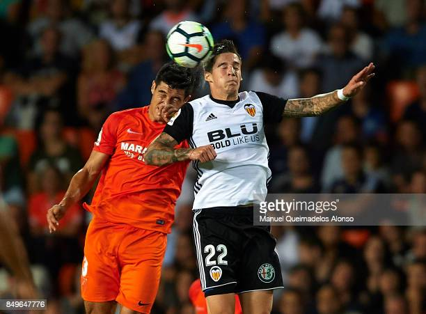 Santi Mina of Valencia competes for the ball with Diego Gonzalez of Malaga during the La Liga match between Valencia and Malaga at Estadio Mestalla...