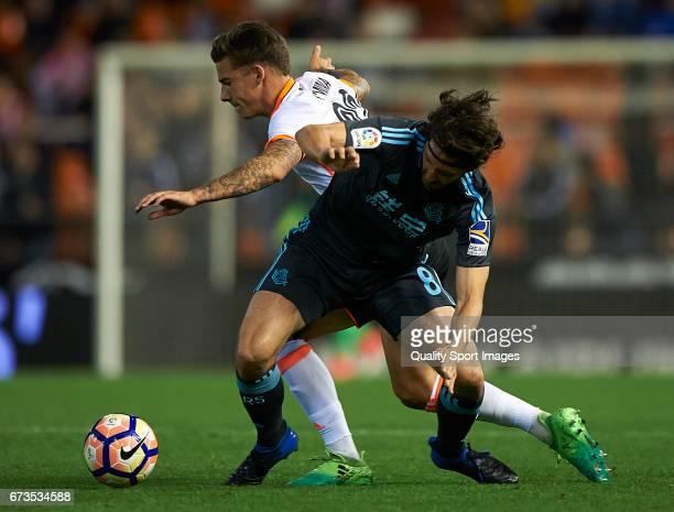 Santi Mina of Valencia competes for the ball with Esteban Granero of Real Sociedad during the La Liga match between Valencia CF and Real Sociedad de...