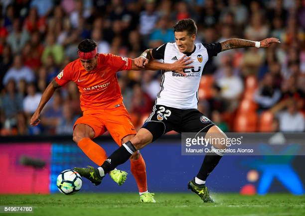 Santi Mina of Valencia competes for the ball with Luis Hernandez Rodriguez of Malaga during the La Liga match between Valencia and Malaga at Estadio...