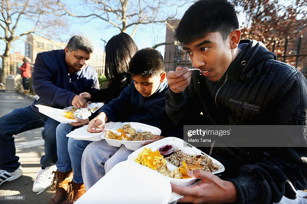 Santiago, Anthony, Natalia and Julio Munoz eat a donated Thanksgiving dinner in the Rockaway neighborhood on November 22, 2012 in the Queens borough of New York City. A number of organizations are providing free Thanksgiving meals for residents of the Rockaways which was hard hit by Superstorm Sandy.