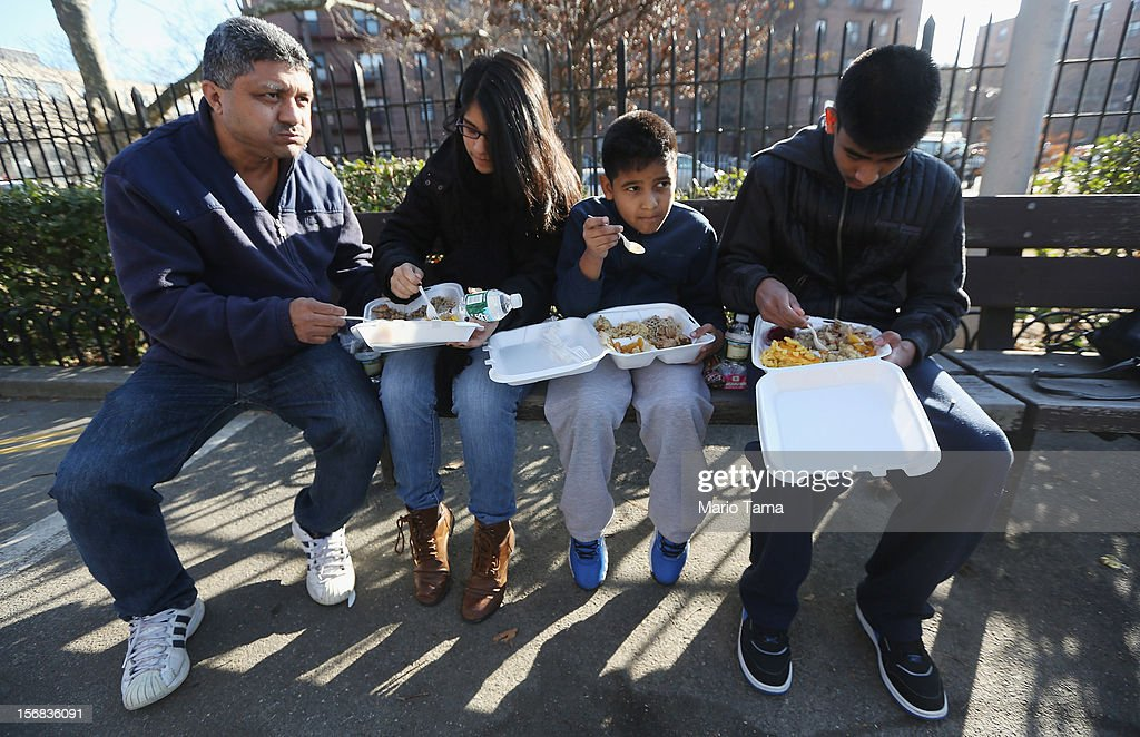 Santiago, Anthony, Natalia and Julio Munoz eat a free donated Thanksgiving dinner in the Rockaway neighborhood on November 22, 2012 in the Queens borough of New York City. A number of organizations are providing free Thanksgiving meals for residents of the Rockaways which was hard hit by Superstorm Sandy.