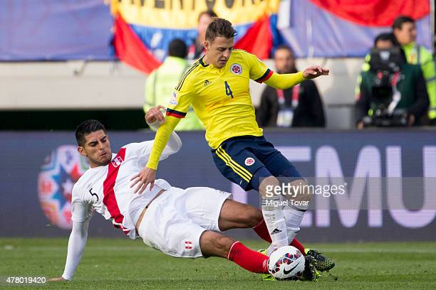 Santiago Arias of Colombia fights for the ball with Carlos Zambrano of Peru during the 2015 Copa America Chile Group C match between Colombia and...